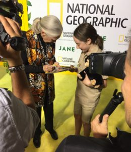 Dr. Jane Goodall signs a vintage copy of National Geographic bearing her face for a young fan.